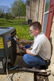 HVAC contractor in Brighton Colorado repairs a condensor unit